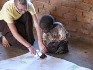 Zoey Petitt, painting with a child from Kamweko village.